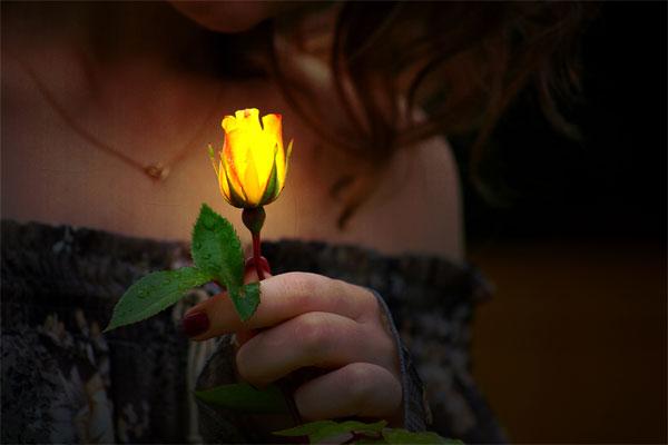 Donna con fiore illuminato di spiritualità