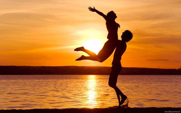 Coppia felice sulla spiaggia al tramonto